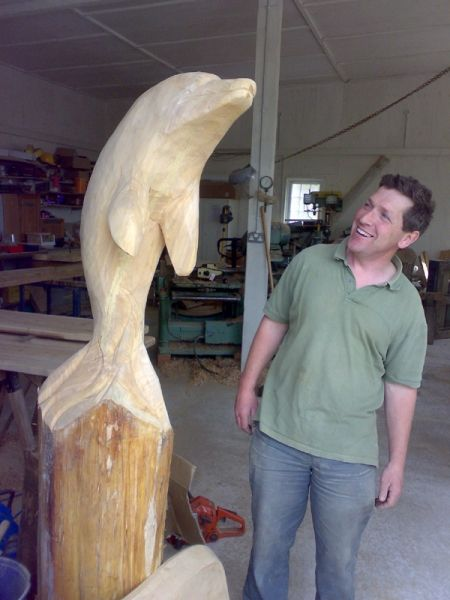 man looking at wooden dolphin carving on a plinth
