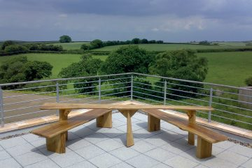 Wooden All Ability Picnic Table Bench installed on paving overlooking fields and woodland