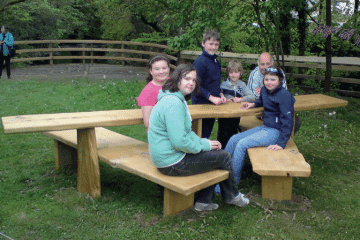 Children sitting at an All Ability Picnic Table Bench near Okement river