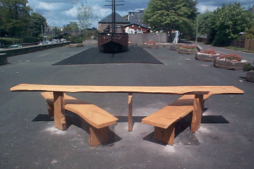 Wooden easy access Picnic Table Bench in front of boat by river
