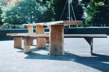 All Ability wooden Picnic table with bench installed on tarmac by a river