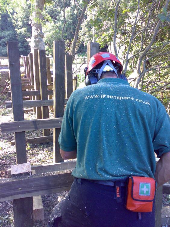 carpenter using laser level to install boardwalk piles