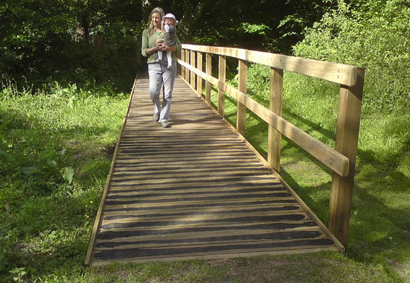 Lady carrying a child on a boardwalk connecting to a path