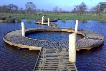 Boardwalk over water with circular pond dipping area