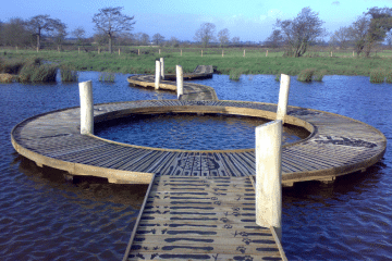 circular viewing boardwalk with animal footprint tread pattern over water