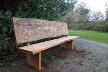 Wooden bench with Salmon artwork carved into backrest