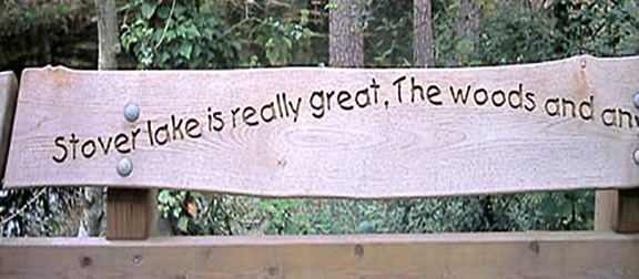 wooden handrail with child's writing carved into it