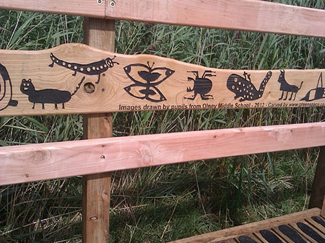 wooden rail with etched children's drawings