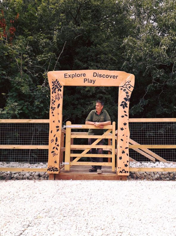 man leaning on a wooden gate under a carved sign