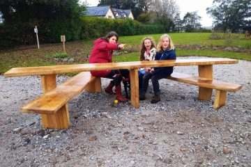 young family sitting on a wooden bench in a park