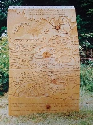 wooden board with wildlife images carved into it